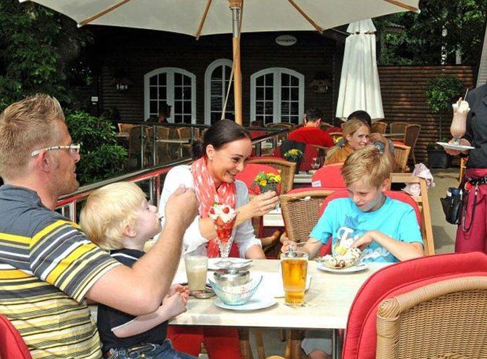 Familie unter Sonnenschirm auf der Restaurant-TerrasseTerrasse