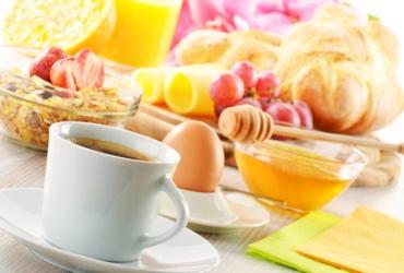 Frühstücksgedeck mit Brötchen, Kaffee, Ei, Honig, Müsli