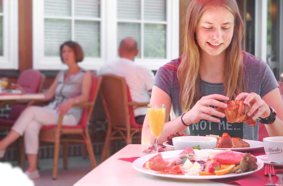 Junge Frau frühstückt auf der Terrasse des Wildpark-Retraurants