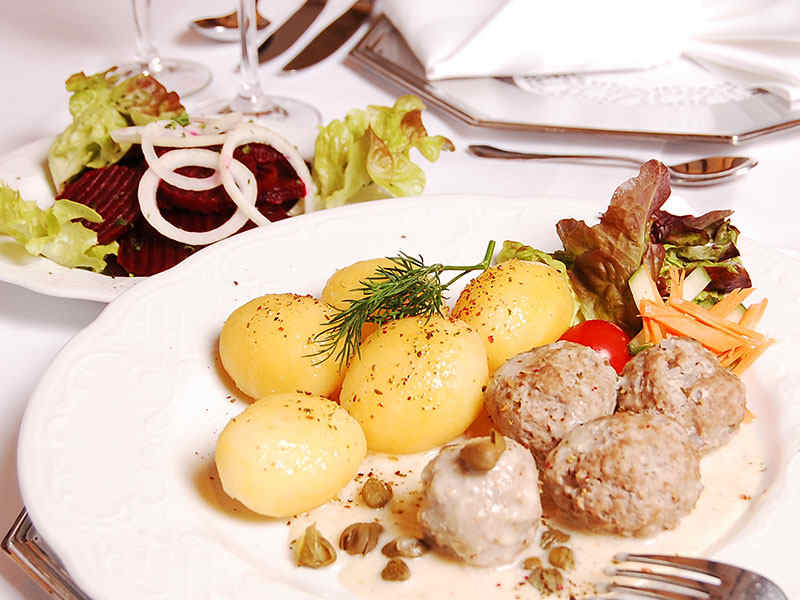 Teller mit Königsberger Klopsen, Kartoffeln und Salat im Wildpark-Restaurant