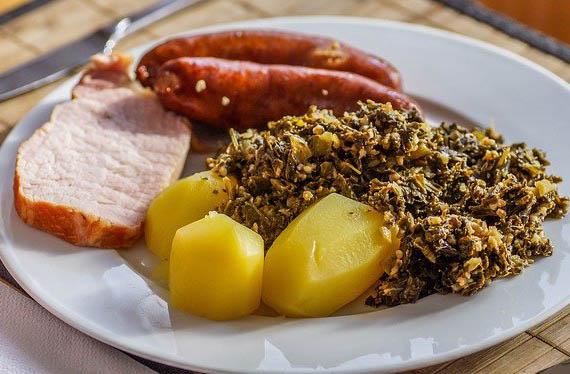 Teller mit Grünkohl mit Kohlwurst, Kassler und Salzkartoffeln